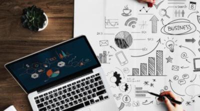 Cheltuieli eligibile Start-Up Nation - o masa cu un laptop si un plan de business pe care se vad tot felul de desene sugestive: bec, pie chart, telefon, grafic cu bare, cana de cafea structura organizationala.