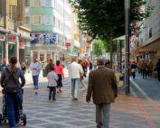 Persoane care trec pe o strada urbana, imaginea este raspuns la intrebarea Cine poate accesa fonduri europene. In dreapta si stanga, pe marginea strazii pietonale se vad siglele magazinelor.