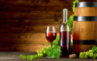 Consultnata Fonduri Europene programul Vitivinicol, se pot obtine fonduri pentru productia de vin (utilaje, spatii) sau deschidere crame. Un pahar de vin plin cu vin rosu si o sticla langa el, o ciorchina de struguri albi si un butoi.
