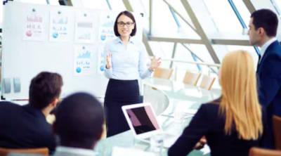 Consultanta Fonduri nerambursabile POR 2.2, o femeie de afaceri care prezinta rezultatele firmeiin ata unui grup. Graficele sunt listate pe hartie si afisate pe un white board.