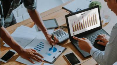 Grafice de business pe laptop si pe hpint de hartie, puse pe o masa, consultanta POR 2.2 SUD Muntenia fonduri europene