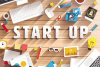 Consultanta Finantare Europeana pentru pornirea unei afaceri: o masa / birou cu obiecte de business start-up agende, ochelari, telefon, aparat de fotografiat, creion, mouse, laptop, cana de ceai, post-it-uri.