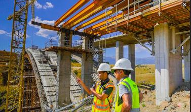 Neotrust ofera consultanta pentru Programul Operational Regional. Prin POR 2.2 se poate construi sediu de firma - doi muncitori privesc spre constructia ridicata de jumate, inca nefinalizata. Ambii poarta casti de protectie.