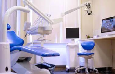 Consultanta Start-Up Nation pentru cabinet stomatologic. Se vede aparatura de specialitate: scaun pacient, scaun medic stomatolog, aparatura lucrari, monitor, totul pe culori crem, alb si albastru.