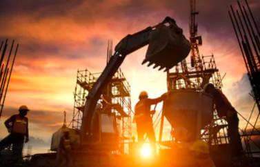 Consultanta Start-Up Nation pentru afaceri in domeniul constructii. Soarele apune, un constructor pe santier lucreaza, se vede cupa escavatorului si soarele cum apune printre schele.