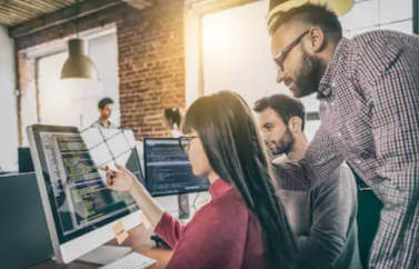 Consultanta Start-Up Nation pentru deschiderea unei firme de IT. In prim plan o programatoare care isi prezinta munca direct de pe monitoriar doi colegi citesc codul.