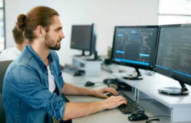 Neotrust ofera consultanta Start_up Nation pentru firma de IT. In imagine este un programator cu doua monitoare in fata, cu mainile pe tastatura, scriind cod.