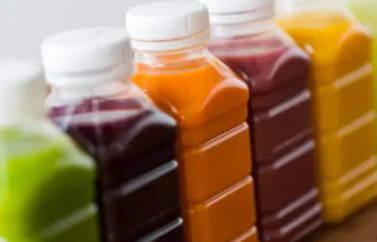 Fonduri Europene Agricultura pentru deschiderea unei fabrici de sucuri naturale. Observam sticle pline cu sucuri naturale, proaspat stoarse, diverse culori: verde, visiniu, mov, roz, portocaliu, galben.