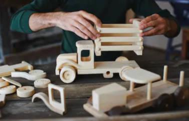 Fonduri europene nerambursabile pentru persoane fizice, un domn asambleaza o jucarie de lemn: camioneta. Langa ea o masina de epoca nalacuita isi asteapta randul.
