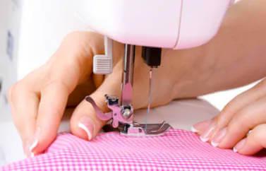 Fonduri Europene Nerambursabile pentru productie - oferim consultanta accesare. O masina de cusut, o mana de doamna cu unghii frenchmanicure, care coase un obiect vestimentar in carouri roz si alb.
