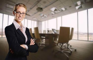 Neotrust consultanta fonduri europene nerambursabile pentru servicii. O tanara care lucreaza in domeniu zambeste cald intr-o sala de conferinte.