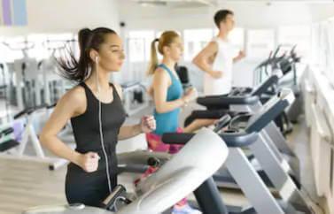 Sala de fitness deschisa din fonduri nerambursabile pentru femei. Doua domnisoare si un domn se vad alergand pe banda de alergat. Cea din prim plan asculta muzica in casti si este imbracata in negru. Urmatoarea are vestimentatie mai colorata: labastru si roz.