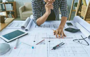 Fonduri Europene pentru un birou de arhitectura. Un arhitect tine creionul in mana, si mana pe barbie, in fata unei planse cu un plan a unei cladirti.