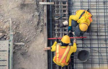 Fonduri europene pentru start-up in constructii, doi muncitori care lucreaza pe nivelul de sus al unei cladiri in constructie. POarta casti de protectie si haine galbene cu veste portocalii.