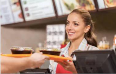 Fonduri Europene pentru un fast food, de tip start-up. O domnisoara care serveste clientii zambeste oferind tava cu comanda. In spate reclamenle luminoase sunt pozitionate alaturi de meniu.