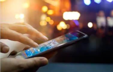 Aplicatie pe telefon, afacere demarata cu fonduri europene pentru tineri. Un telefon butonat pe strada, iar in departare se vad luminitele orasului.