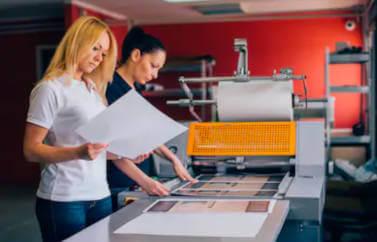 Fonduri Europene pentru tineri: doua doamne stau in fata unui printer verificand creatia. peretele din spate este rosu, iar printerul gri/albastru si portocaliu.