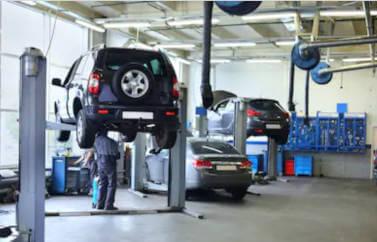 Avem fonduri europene pentru tineri pentru deschiderea unui service auto. Masinile sunt ridicate pe platforme pentru reparatiiin hala serviceului.