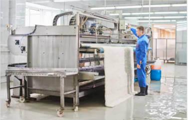 Fonduri Europene Tineri pentru o spalatorie de covoare: un muncitor apasa pe un buton pentru stoarcerea covorului prin utilaj. Este imbracat in albastru si poarta cizme de cauciuc pentru a se proteja in mediul umed.
