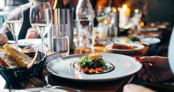 Fonduri Europene pentru turism si activitati turistice: restaurant, o farfurie pe masa cu mancare french style cooking..Cosul cu paine imbie clientii. Paharele aranjate langa farfurie stralucesc de curatenie.