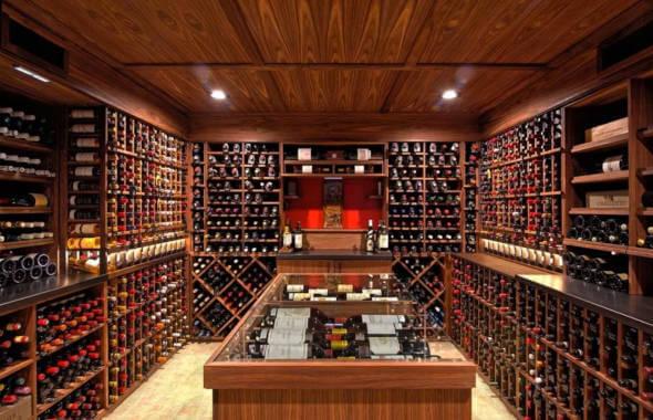 Interiorul camerei de degustare a unei crame, cu nenumarate sticle aranjate pe rafturipe perete si o masa mare cu capac de sticla in mijlocul incaperii. Sub capac sunt aranjate alte sticle de vin. Prin serviciul de consultanta program vitivinicol se pot construi crame, amenaja camere de degustare sau camere laborator.