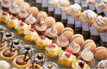 Pentru un laborator de cofetarie patiserie se pot accesa fonduri nerambursabile pentru femei. In imagine se vad prajituri gustoase diverse sortimente, aranjate frumos pe randuri.