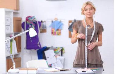 Nenumarate oportunitati de finantare cu fonduri nerambursabile pentru femei, iar una dintre ele este atelierul de croitorie. O tanara care sta cu centimetrul de croitorie dupa gat, zambind, la biroul ei de creatie vestimentara. In spate se vede un maechin imbracat cu o bluza mov, o lampa, , probabil pe birou. Femeia este blonda, imbracata lejer cu un tricou maro deschis.