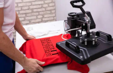 "O idee de afaceri pentru programul Start-Up Nation este un atelier de imprimare digitala pe materiale textile, in prim plan este o imprimanta digitala care imprimeaza pe un tricou textul ""Make It Happen""."