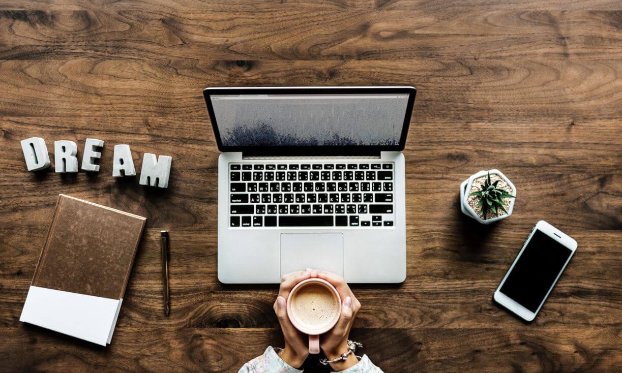 Misiune Neotrust - un birou de lemn cu laptop, telefon, cana de cafea.