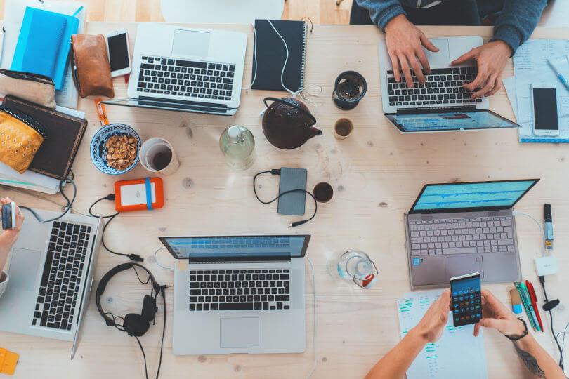 Un birou plin cu diverse obiecte: laptop, agenda, ceainic, telefon, farfurie cu coji de alune, pixuri, markere, casti, incarcator, sticla de apa, portmoneu,. Se vad si mainile: o pereche tastand la laptop, o pereche butonand pe telefon. Consultanta pentru calcul Punctaj Start-Up Nation.
