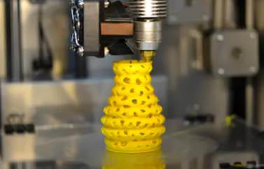 Accesare fonduri europene Oradea pentru activitati de imprimare 3D. Se vede o masina deprint 3D care printeaza o structura complexa de culoare galbena.