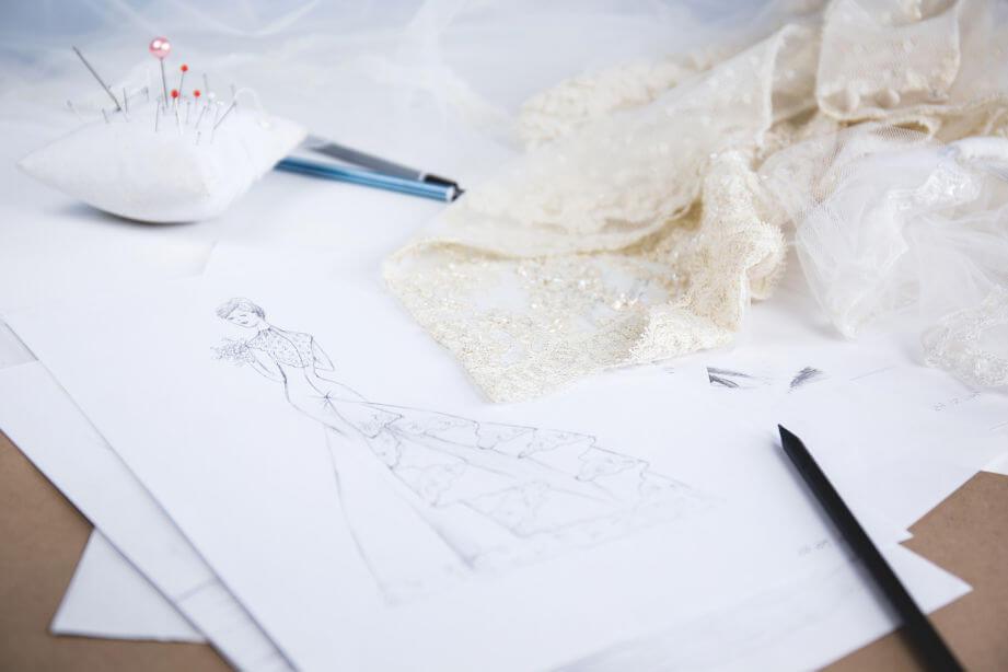 Un atelier de croitorie este un dintre cele mai bune idei de afaceri cu fonduri europene nerambursabile pentru tineri. Se vede o foaie alba de hartie pe care e desenata un model de rochie s, un creion, o pernita in care sunt infinse ace de gamali, unele cu bilute in capat si o bucata eleganta de dantela alba.