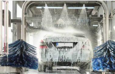 Consultanta Fonduri Europene Startup Nation Laborator Cofetarie Patiserie - o masina gri plina e spuma alba, intr-o spalatorie, stropita de jeturi de apa.