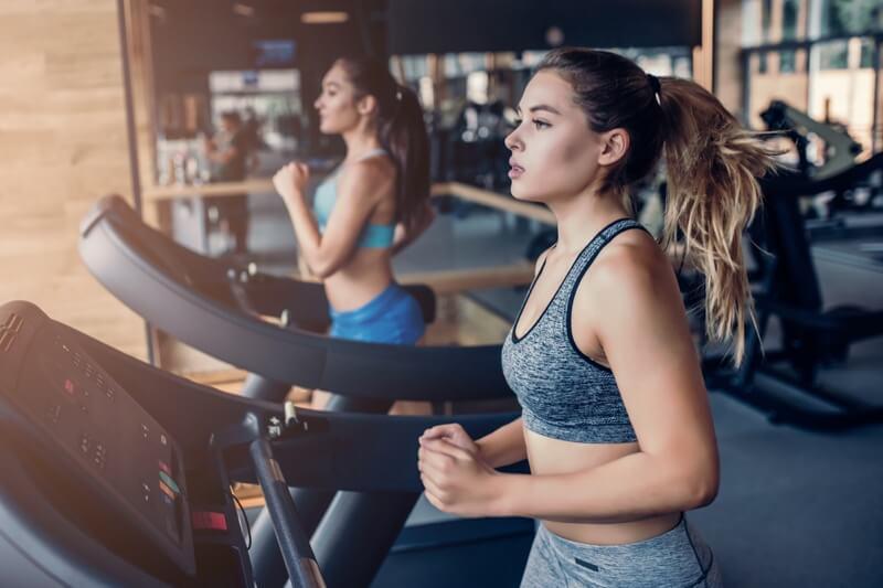 Sala Fitness deschisa cu fonduri europene: doua tinere care alearga pe banda, imbracate in echipament sportiv privesc in departare pe geam. In fundal se observa alte echipamente utilizae intr-o sala de fitness.