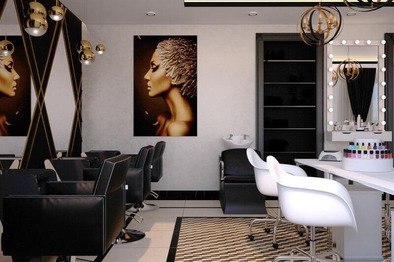 Salon de infrumusetare pe fonduri europene: scaune pentru coafor negre, comode cu burete asezate in fata unor oglinzi, scaune albe petru machiaj si manichiura in fata carora se vad sticlude de lac de unghii, un saun epntru spalat par, cu o chiuveta alba langa el, iar pe perete se vede un tablou si o usa.