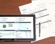 Un birou cu o tableta pe care se vede un grafic de crestere: este prezentat profitul in crestere. Si langa se vad doua rapoarte, simbolizand latura profitabila a accesarii de fonduri guvernamentale prin servicii de consultanta
