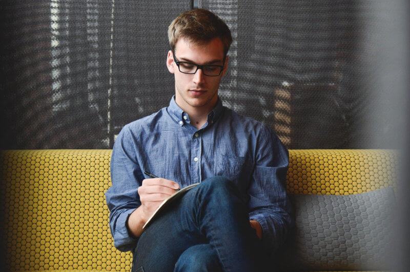 Cum se pregateste un proiect de fonduri europene in 2020 - un tanat antreprenor imbracat cu o camasa albastra, cu ochelari cu rame negre, sta la pe o canapea galbena si scrie un plan de afacere la laptop.o canapea