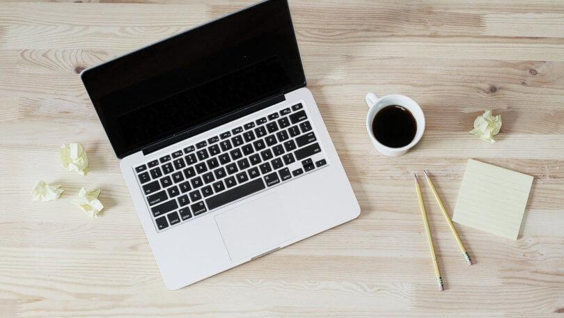 Idei de Afaceri Profitabile pentru Incepatori in anul 2020 - se vede un lptop, o cana alba de cafea neindulcita neagra, doua creioane, post-it-uri galben deschis si cateva postituri mototolite pe care au fost scrise idei de afaceri.