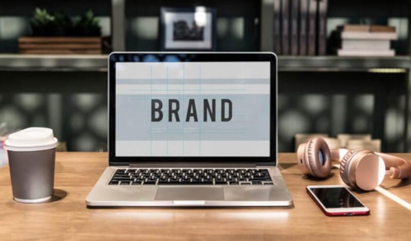 Nume de firme Ghid Alegere Dennumire, Idei Firma StartUp se vede un laptop pe care scrie Brand, asezat pe un birou de lemn.